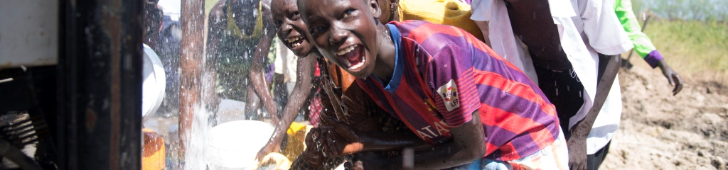 Children from Payuen react to the drilling of new bore hole which JFSP have confirmed as the biggest volume of water discovered to date in Jonglei.